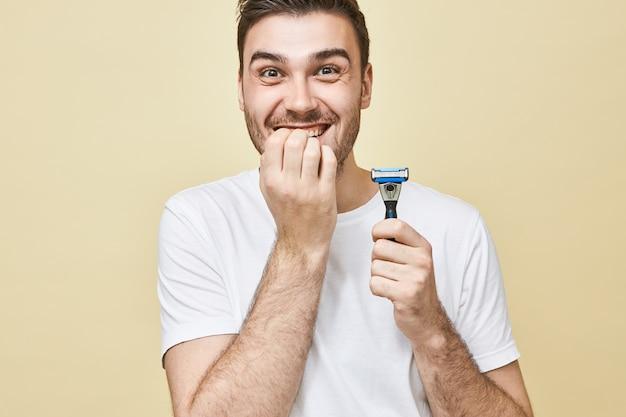 피부 관리, 남성의 아름다움과 남성 성 개념. 면도 면도기를 들고 흰색 티셔츠에 감정적 인 젊은 갈색 머리 남자, 긴장된 표정을 가지고, 손톱을 물고, 처음으로 면도하는 것을 두려워