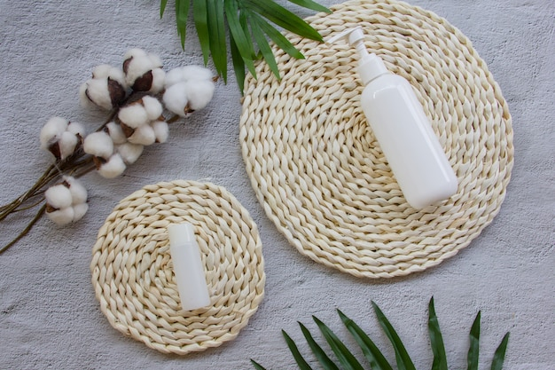 Skin care mock up bottle on wicker pad with cotton flowers and palm leaves