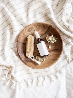 Коричневая бутылка для ухода за кожей и деревянная щетка в миске на полотенце в ванной, плоская планировка. вид сверху, копировать пространство