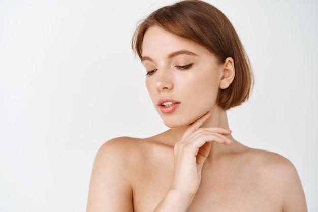 피부 관리. 짧은 머리를 가진 자연적인 젊은 여성, 화장 없이 부드러운 얼굴 피부를 부드럽게 만지고 흰 벽에 벌거벗은 어깨를 서 있습니다. 아름다움과 메이크업 개념