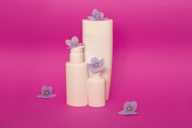 보라색 꽃 가운데 분홍색 배경에 스킨 케어 포장 모형. 평평하다. 천연 화장품 미용. 얼굴 및 신체 치료. 공간을 복사하십시오. 전면보기.
