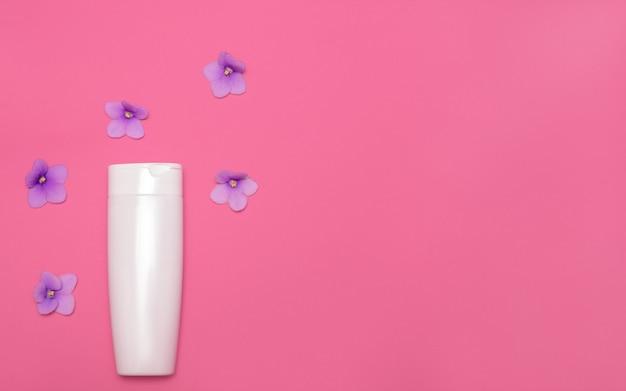 보라색 꽃 가운데 분홍색 배경에 스킨 케어 포장 모형. 평평하다. 천연 화장품 미용. 얼굴 및 신체 치료. 공간을 복사하십시오. 평면도