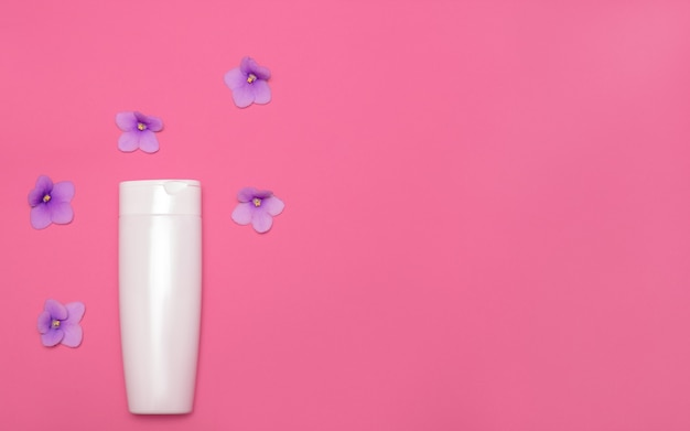 Skin care packaging mockup on a pink background among violet flowers. flat lay. cosmetic beauty natural. face and body treatment. copy space. top view