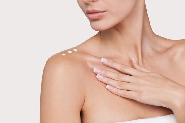 Забота о коже. часть красивой молодой женщины со сливками на плече, стоящей на сером фоне