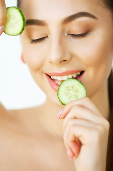 Skin care. portrait beautiful happy woman with cucumbers to eyes at home. beauty treatment. cosmetology. beauty spa salon