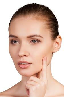 Уход за кожей. портрет красивой молодой женщины без рубашки, держащей палец на щеке и смотрящей в камеру, изолированную на белом фоне