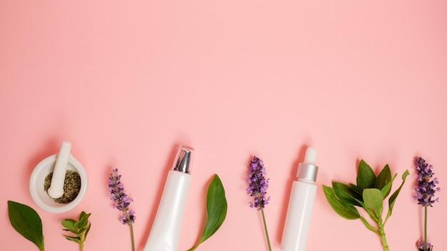 핑크 플랫 누워 배경에 스킨 케어 제품. 초본과 라벤더를 가진 유기 아름다움 정유. 건강을위한 아로마 테라피