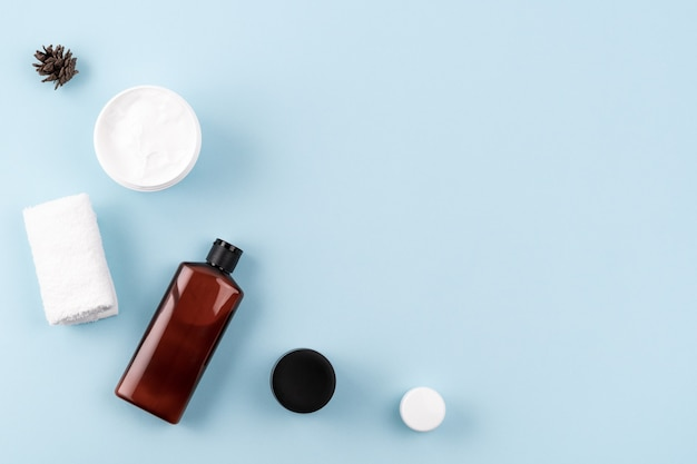 Skin care products on blue surface. frame from shampoo or cosmetic lotion bottle, towel, open facial cream jar. beauty, spa composition. natural cosmetic concept. flat lay, layout, copy space