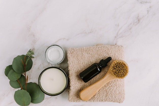 Skin care products flat lay  body or face brush and serum bottle on beige towel aroma candle