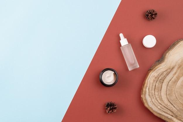 スキンケア商品。オープンクリームジャー、ペプチド入り美容液、木製断面カット、茶色と青色の表面に松ぼっくり。美しさ、スパのコンセプト。フラットレイ、レイアウト、コピースペース、上