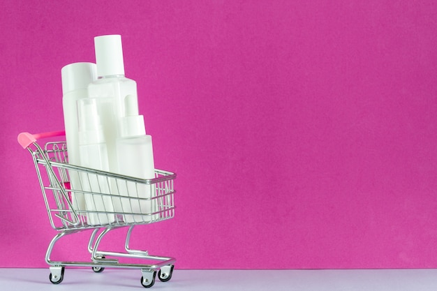 Skin care products  in shopping trolley cart. cream lotion spray serum oil, hyaluronic acid