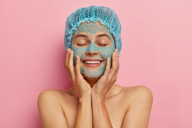 Skin care routine concept. beautiful satisfied woman touches cheeks gently, applies nourishing sea salt facial scrub, satisfied by spa therapy, smiles broadly, wears blue waterproof headgear