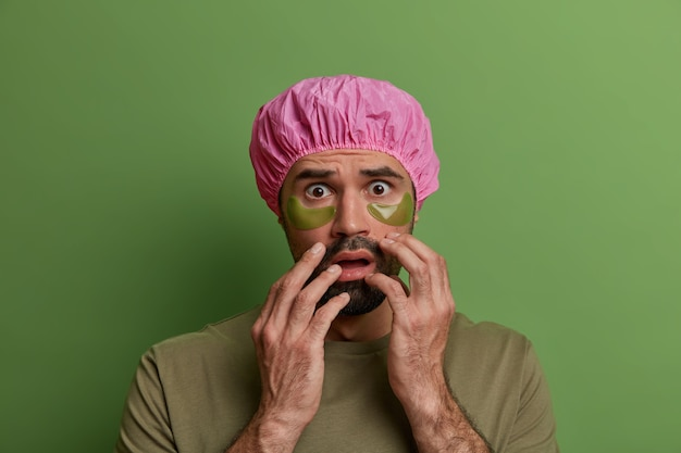 Регулярный уход за кожей, уход за лицом. испуганный европейский парень носит коллагеновые пятна под глазами, заботится о лице, носит водонепроницаемую шапочку для душа, одет в повседневную футболку, изолированную на яркой яркой стене.