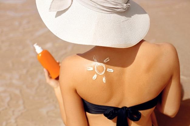 スキンケア。日焼け止め。ビキニの美しい女性は顔に日焼け止めクリームを適用します