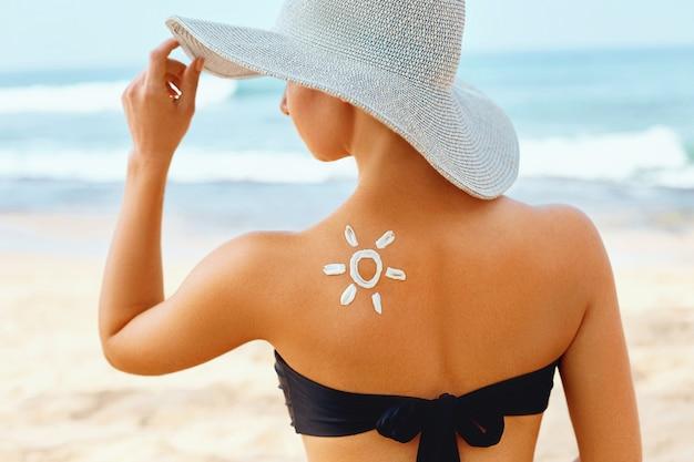 スキンケア。日焼け止め。ビューティーウーマンは日焼け止めクリームを塗ります。太陽の形でビーチで日焼け止めローションを持つ女性。