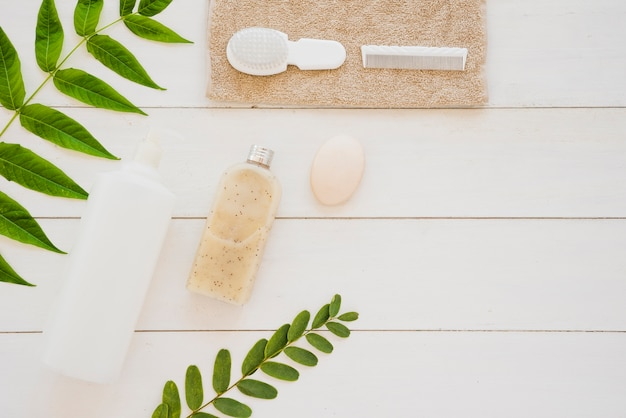 Skin care tools on desk with green leaves