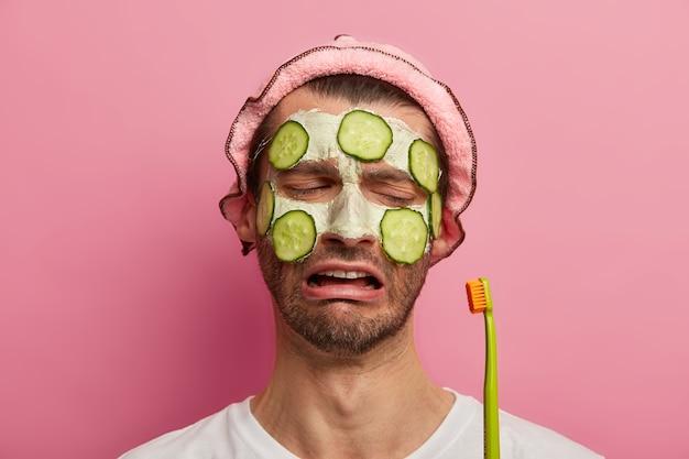 피부 관리 치료 개념. 슬프게 불만족스러운 남자는 슬프게 칫솔을보고 수염이 있고 오이로 화장품 마스크를 바릅니다.