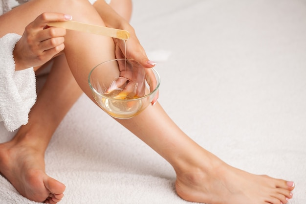 Skin care, a woman applies wax to her leg to remove hair.