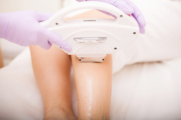 Skin care. woman at cosmetics salon, legs laser epilation.