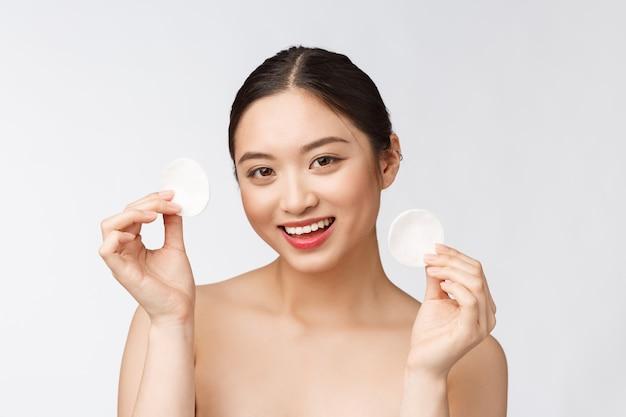 Уход за кожей женщина, удаляющая макияж с ватного тампона - концепция ухода за кожей лицо крупным планом красивой модели смешанной расы с идеальной кожей