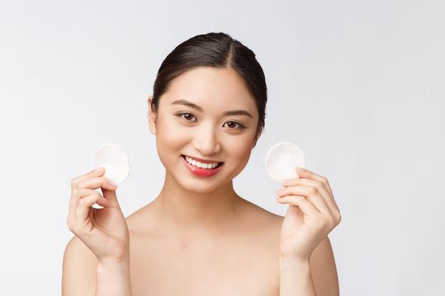 면봉 패드와 얼굴 메이크업을 제거하는 피부 관리 여자-스킨 케어 개념 완벽한 피부와 아름다운 혼혈 모델의 얼굴 근접 촬영