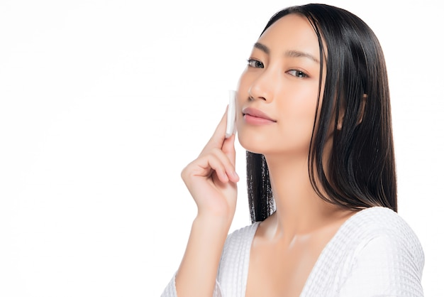 Skin care woman removing face makeup with cotton swab pad.