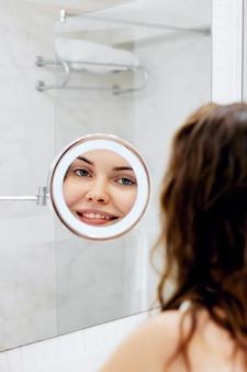 피부 관리. 여자 머리를 만지고 거울을 보면서 웃 고. 욕실에 젖은 머리를 가진 행복 한 여자의 초상화