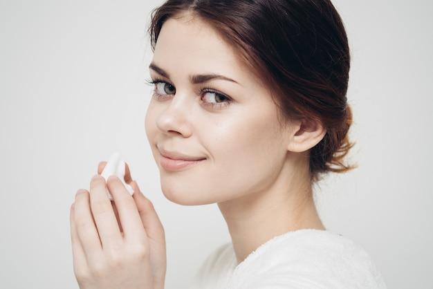 피부 관리 여자는 흰색 스폰지로 그녀의 얼굴을 닦습니다.
