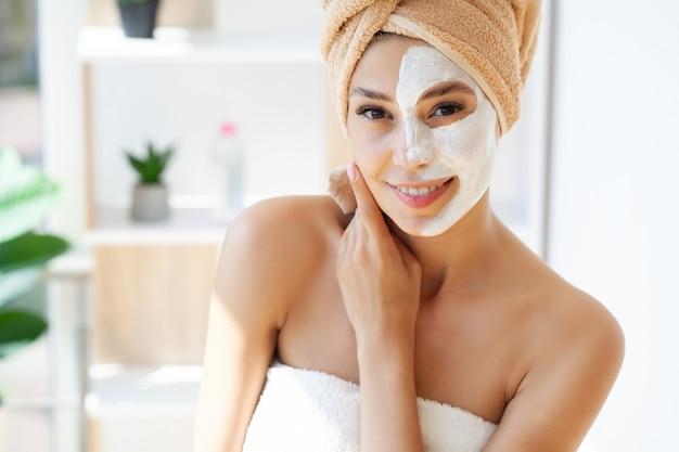 Уход за кожей, женщина с красивой кожей лица, применяя маску на лице.