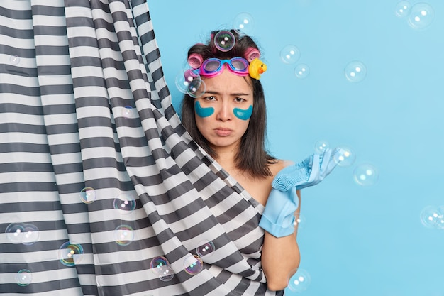 Skin care women beauty hygiene concept. dissatisfied brunette asian woman frowns face applies collagen patches hair curlers wears rubber gloves poses behind shower curtain