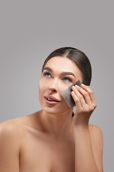 Skin care. young woman removing oil from face using blotting papers. beautiful girl model with smooth and healthy skin.