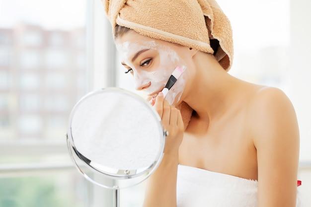 Уход за кожей, молодая женщина с красивой кожей лица, применяя маску на лице