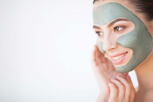 Skin care. young woman with cosmetic clay mask holding cucumber at her bathroom