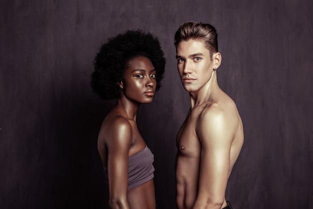肌の色のコントラスト。肌の色が違う魅力的な真面目な人が向かい合って立っている