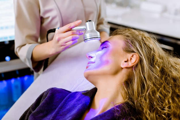 Skin cosmetology. woman beautician doing blue light therapy on face of pretty young blond woman