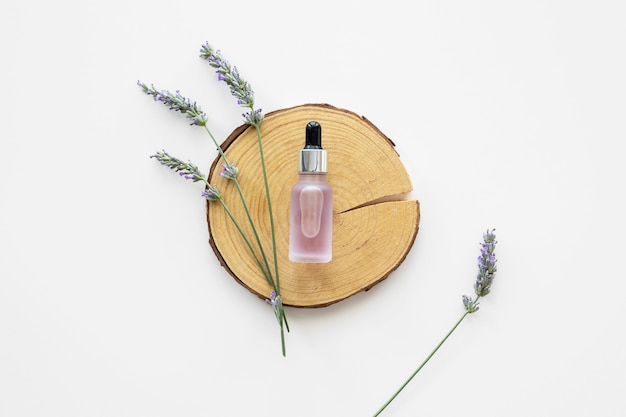 Skin oil and flowers flat lay