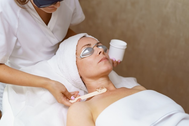 Skin rejuvenating, treatment or therapy. dermatologist applying lotion on female skin. customer lying with protective glasses in the beauty salon relaxing