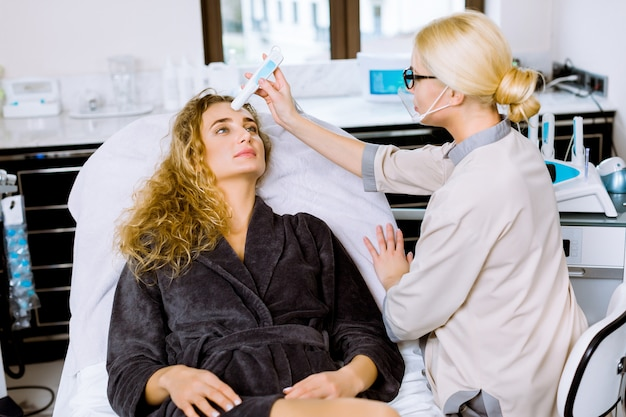 Омоложение кожи, электромагнитная импульсная терапия. молодая красивая женщина лежит на диване в современном спа-центре, женщина-врач косметолог в форме делает процедуру
