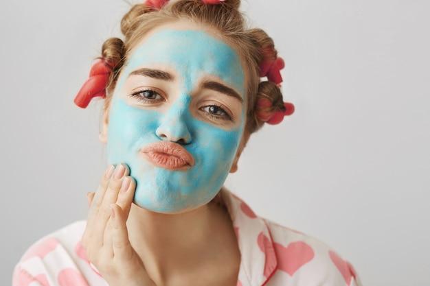 스킨 케어 및 뷰티 개념. 머리카락 curlers 및 잠옷 소녀는 얼굴 마스크를 적용