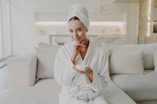 Концепция ухода за кожей и красоты. портрет молодой привлекательной женщины в халате и полотенце на голове, держащей банку с кремом и улыбающейся, сидя на диване в гостиной, делая косметические процедуры