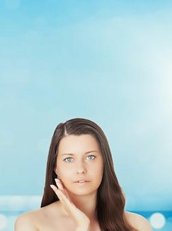 背景の美しさの健康と旅行の概念の美しい若い日焼けした女性青い海と空の夏の肖像画のスキンケアと日焼け止め