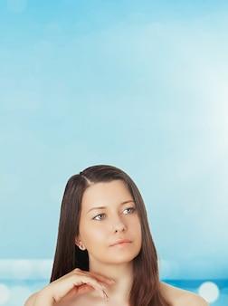 Уход за кожей и защита от солнца портрет красивой молодой загорелой женщины синего моря и неба на фоне красоты, здоровья и концепции путешествий