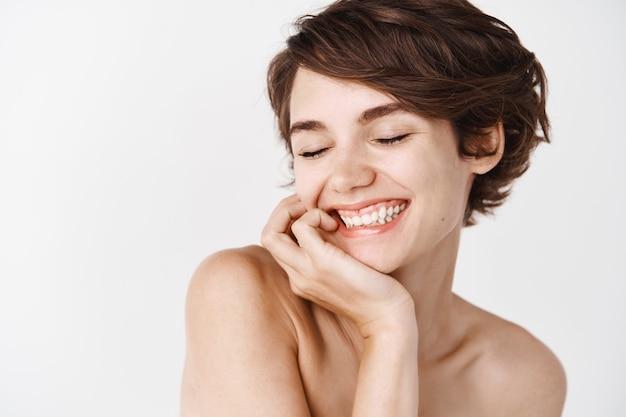Уход за кожей и женская красота. девушка с естественным взглядом улыбается, стоя на белой стене обнаженным телом. концепция ежедневного ухода и душа