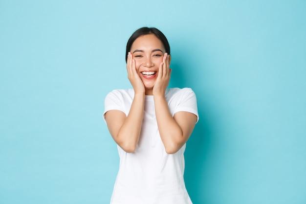 スキンケア、美容、ライフスタイルのコンセプトです。陽気な笑顔のアジアの女の子の喜び、幸せそうに見えて、完全にきれいな肌に触れて、喜び、にきびを取り除き、青い壁に立っています