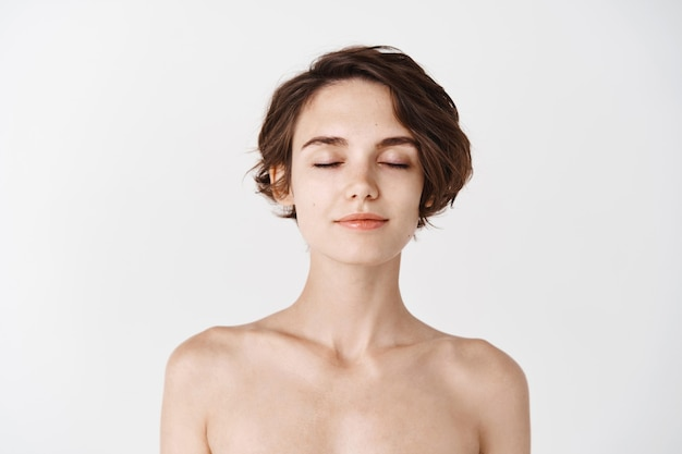 Skincare and beauty. close-up of young woman with no makeup and naked shoulders, close eyes and smiling tenderly, enjoying fresh and clean feeling after shower, white wall