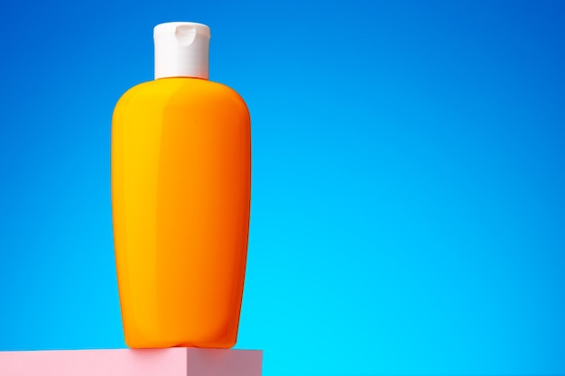 Контейнер для косметических товаров по уходу за кожей на синем фоне, копией пространства