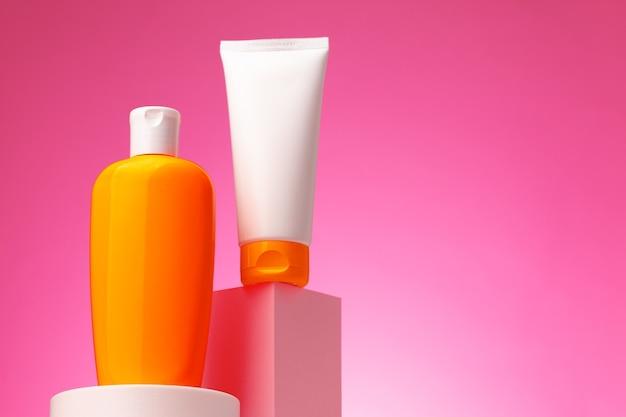 Контейнер для косметических товаров по уходу за кожей на розовом фоне, копией пространства