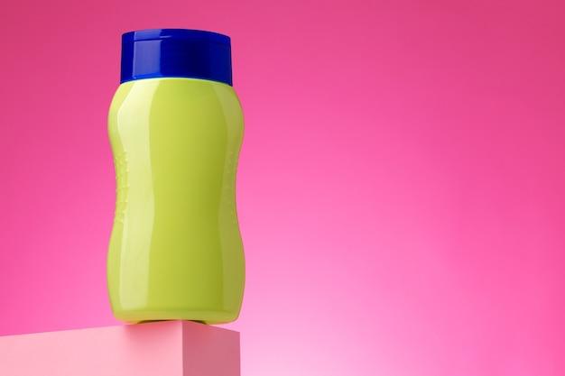 Контейнер для косметических товаров по уходу за кожей на розовом фоне