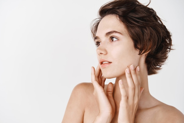 Skincare concept. beautiful young woman standing in profile, touching pure hydrated skin, looking left. girl with naked shoulders and short hairstyle shows healthy no makeup face, white wall