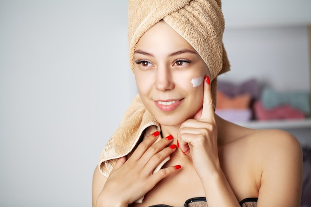 Skincare concept, portrait of happy female applying cosmetic cream on face.